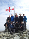 A group on Scafell Pike summit during the three peaks challenge